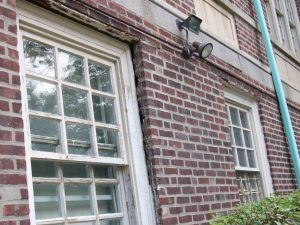 Brick wall leaning outward due to corroding steel angles at window heads