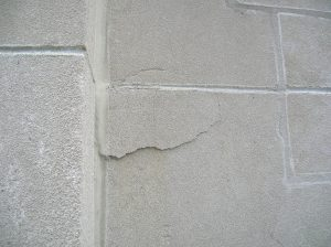 Spalling limestone, held on only by sealant on one side