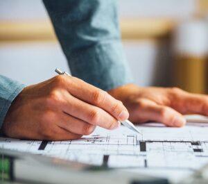 Close up view of Man drawing up blueprints
